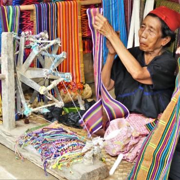 Een vrouw werkt met een spinnewiel.
