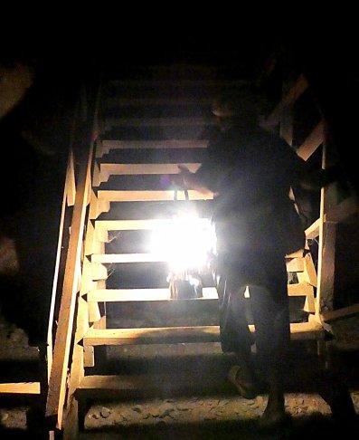 Steile trappen leiden ons door de donkere grot.